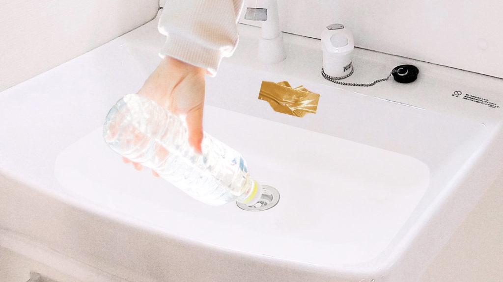 詰まった洗面所の流しにペットボトルを入れる画像